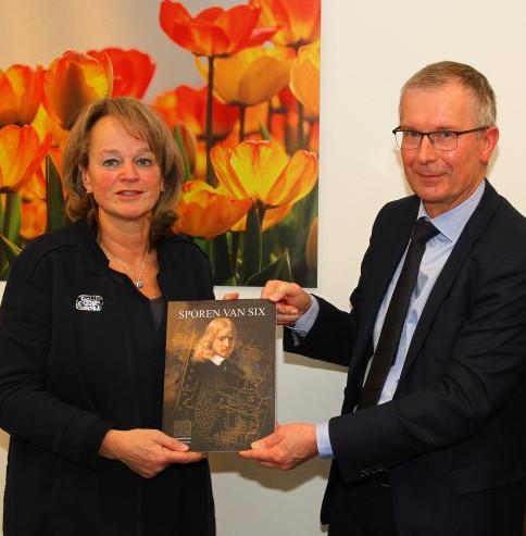 Henk Schaap overhandigt de voorpublicatie van Sporen van Six in Lisse aan Burgemeester Lies Spruit.
